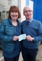 Hector Whitelaw receiving a cheque for £1000 from Marlene Hill of For Bute